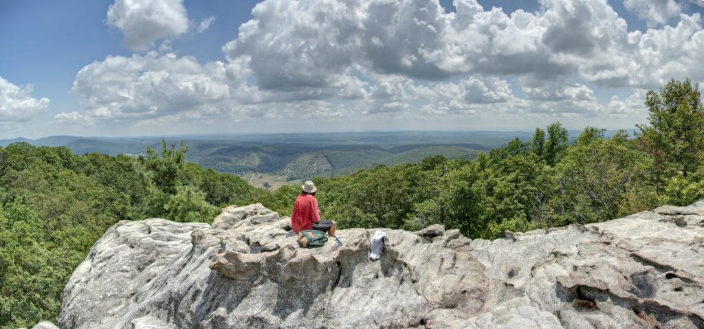 一个徒步旅行者坐在岩石悬崖上俯瞰绿色的树顶和蓝色的天空和蓬松的云