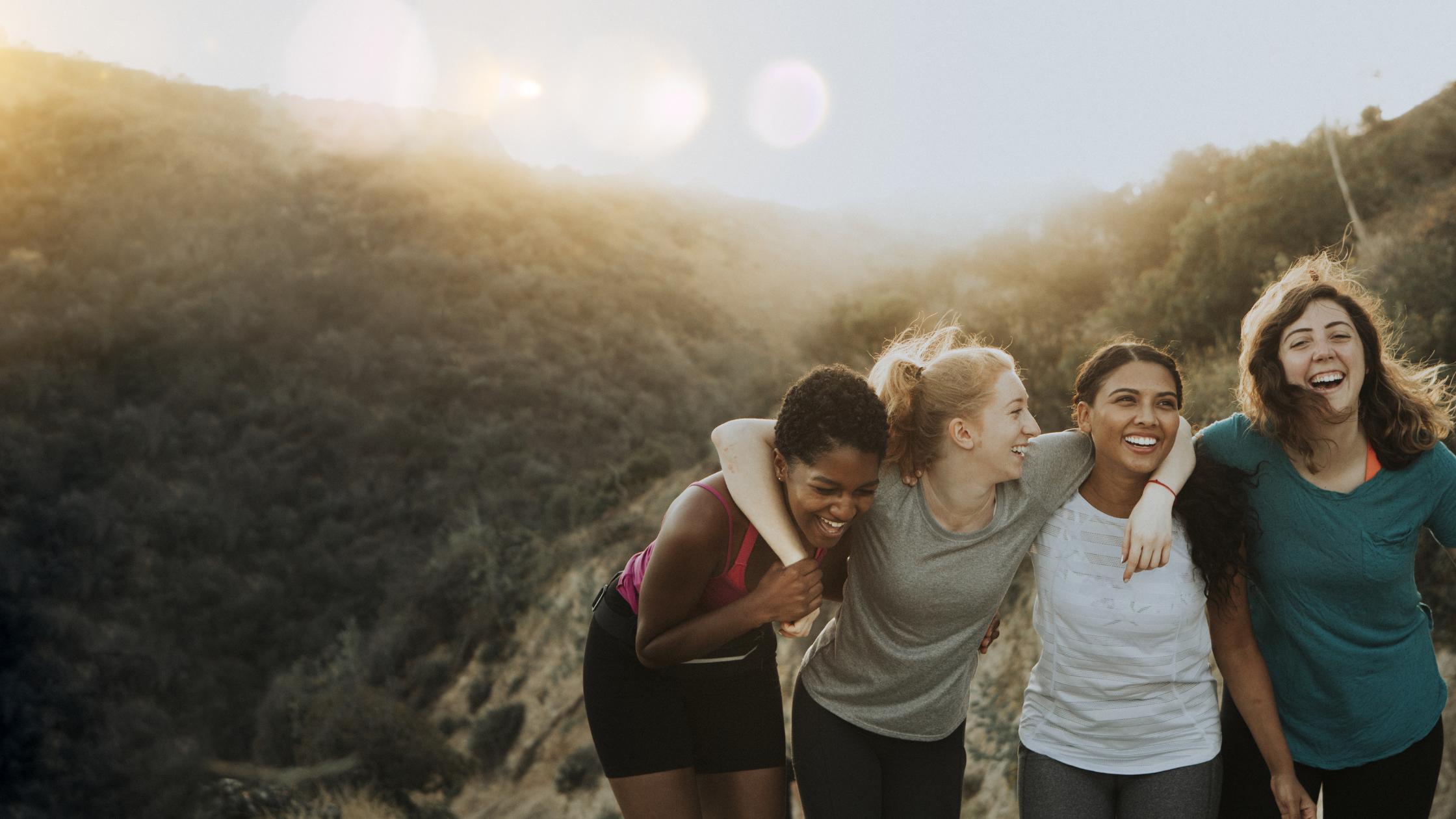 四个朋友徒步穿越起伏的山丘,笑着笑着